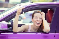 Woman, buyer sitting in her new car showing keys. Closeup portrait happy, smiling, young attractive woman, buyer sitting in her new purple car showing keys Royalty Free Stock Image
