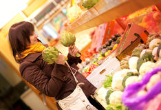 Woman buying artichokes at market Stock Photography