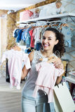 Woman buying baby sleep suit. Smiling woman buying baby sleep suit in kids in apparel shop Royalty Free Stock Images