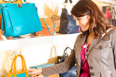 Woman buying a bag in mall. Young happy woman having fun while shopping in a mall, she is looking for a bag Stock Images