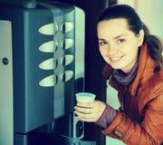 Woman buying beverage in coffee machine. Portrait of glad adult woman buying warm beverage in automatic coffee machine Stock Photography