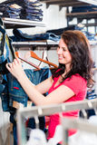 Woman buying blue jeans Stock Photos