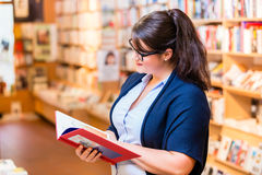Woman buying books in bookstore Stock Photo