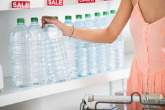 Woman Buying Bottle Of Mineral Water In Supermarket Royalty Free Stock Images