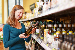 Woman buying bottle of olive oil. Smiling elderly woman buying a bottle of olive oil in a supermarket Stock Photos