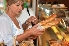 Woman buying bread Stock Images