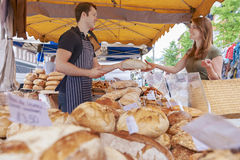 Woman Buying Bread From Market Stall. Customer Buys Loaf From Market Bread Stall stock photo