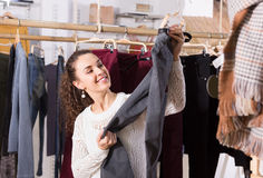 Woman buying breeches at the store. Attractive young brunette selecting new breeches at the store stock photo