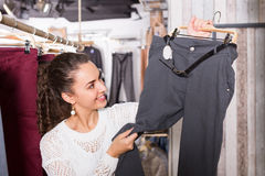 Woman buying breeches at the store. Happy smiling young brunette selecting new breeches at the store stock photos