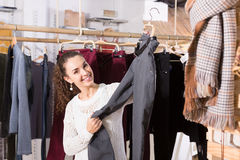 Woman buying breeches at the store. Joyful smiling young brunette selecting new breeches at the store royalty free stock photography