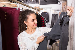 Woman buying breeches at the store. Joyful young brunette selecting new breeches at the store royalty free stock images