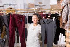 Woman buying breeches at the store. Smiling young brunette selecting new breeches at the store royalty free stock image