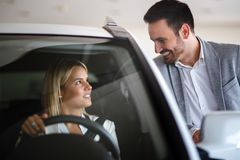 Woman buying a car in dealership sitting in her new auto stock image