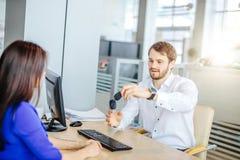 Salesman handing over car key to a customer woman royalty free stock photos
