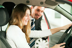 Woman buying car from salesperson. Woman buying a car in dealership sitting in her new auto, the salesman talking to her in the background Stock Image