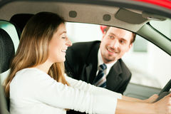 Woman buying car from salesperson. Woman buying a car in dealership sitting in her new auto, the salesman talking to her in the background Royalty Free Stock Photos