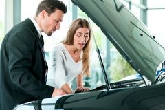 Woman buying car from salesperson. Woman buying a car in dealership looking under the hood at the engine Royalty Free Stock Photos