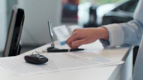 Woman buying a car and signing the contract, model car in the background. stock footage