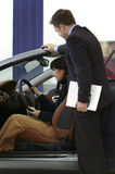 Woman buying car. Young women buying a car in a showroom with sales assistant man Stock Images