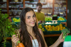 Woman buying carrot and broccoli in supermarket Stock Photography