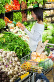 Woman buying carrot in organic section Stock Image