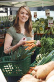 Woman Buying Carrots At Vegetable Stall In Market Royalty Free Stock Photos