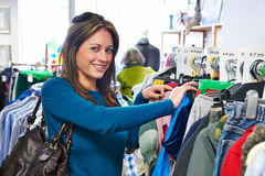 Woman Buying Children's Clothes In Charity Shop. Woman Buys Children's Clothes In Charity Shop Stock Images