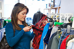 Woman Buying Children's Clothes In Charity Shop. Woman Buys Children's Clothes In Charity Shop Stock Photos