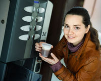 Woman buying coffee from automatic machine Royalty Free Stock Photos