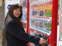 Woman buying coffee in vending machine Stock Photography