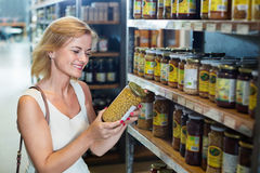 Woman buying conserve peas in glass jar in grocery shop. Portrait of happy positive women buying conserve peas in glass jar in grocery shop Royalty Free Stock Photography