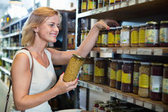 Woman buying conserve peas in glass jar in grocery shop. Portrait of smiling woman buying conserve peas in glass jar in grocery shop Royalty Free Stock Photography