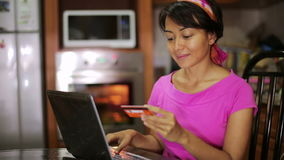Woman buying with credit card, online shopping in kitchen Stock Photos