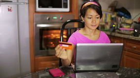 Woman buying with credit card, online shopping in kitchen Stock Images