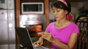 Woman buying with credit card, online shopping in kitchen Royalty Free Stock Photography