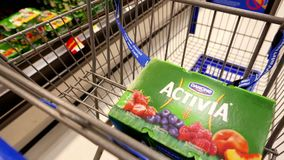 Woman buying Danone Activia strawberry yogurt and putting into shopping cart stock footage