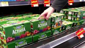 Woman buying Danone Activia yogurt