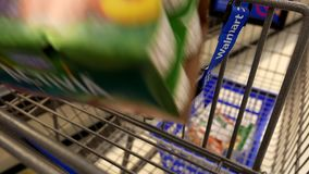 Woman buying Danone Activia yogurt and putting into shopping cart stock footage