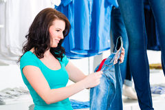 Woman buying fashion blue jeans in shop Royalty Free Stock Photo