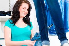 Woman buying fashion blue jeans in shop Royalty Free Stock Photos