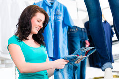 Woman buying fashion blue jeans in shop Stock Images