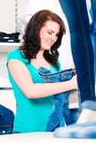 Woman buying fashion blue jeans in shop Royalty Free Stock Images