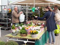Woman buying flowers on a Belgian market. Halle, Belgium - September 26, 2015: Woman buying flowers on a Belgian market royalty free stock photo