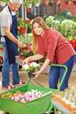 Woman buying flowers in a garden center Stock Photos