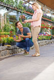 Woman buying flowers in garden center. Smiling young women buying flowers in a pot in a garden center stock image