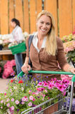 Woman buying flowers shopping cart garden center Royalty Free Stock Photography