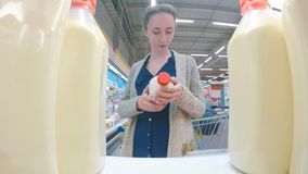 Woman buying fresh milk at supermarket. Woman buying fresh milk at grocery store. Point of view shot. Consumerism, sale, shopping and health care concept royalty free stock photo