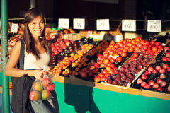Woman buying fruits and vegetables, farmers market. Woman buying fruits and vegetables at farmers market. Candid portrait of young woman shopping for healthy Stock Photo