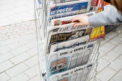 Woman buying German Die Zeit newspaper with Angela Merkel. STRASBOURG, FRANCE - OCT 28, 2017: Woman reading buying German Die Zeit newspaper at press kiosk royalty free stock image