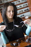 Woman buying glasses. A brunette woman at optician shop, trying on and choosing new glasses Royalty Free Stock Photos